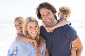 Family photo with two smiling parents and a young boy and girl on their backs